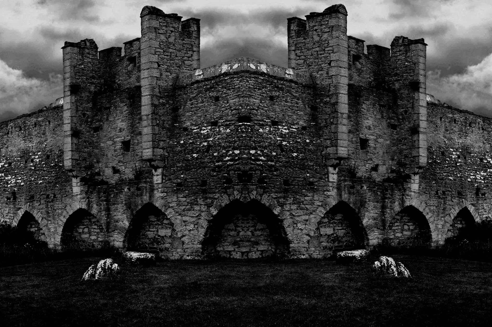 Exterior of a castle wall, black and white.